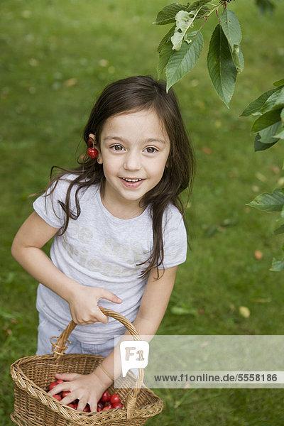 Girl gathering fruit in basket