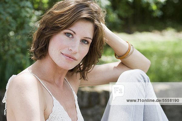 Lächelnde Frau im Freien sitzend