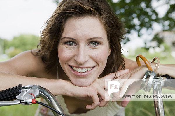 Frau  die sich im Freien auf das Fahrrad stützt