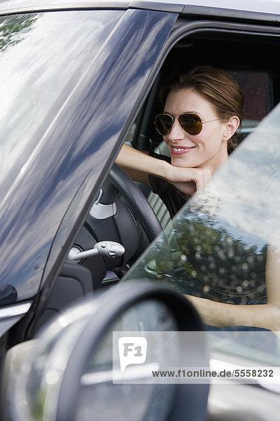 Lächelnde Frau mit Sonnenbrille im Auto