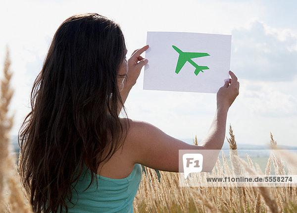 Frau hält Bild vom Flugzeug am Himmel
