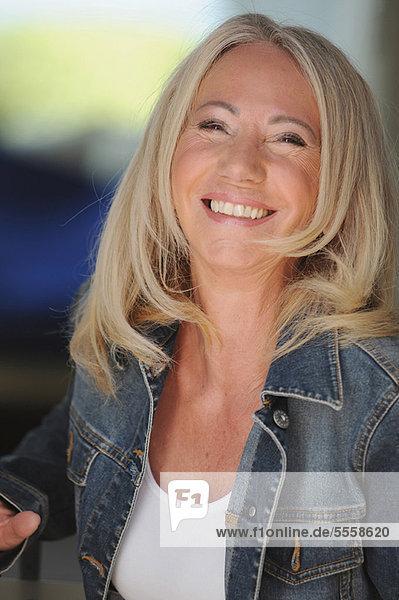 Lächelnde ältere Frau in Jeansjacke