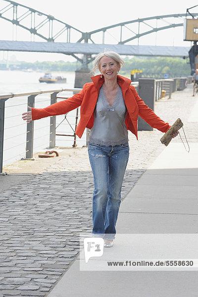Ältere Frau geht am Flussufer entlang