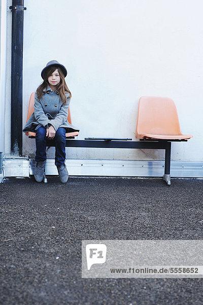 Mädchen sitzend auf Stuhl im Freien