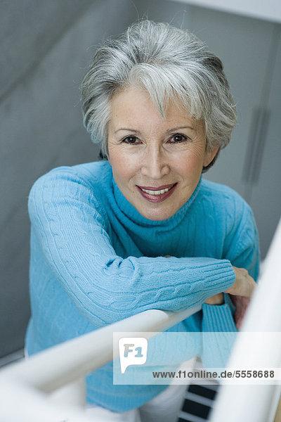 Lächelnde ältere Frau beim Treppensteigen
