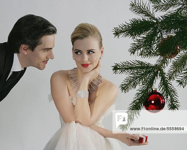 Paar am Weihnachtsbaum sitzend