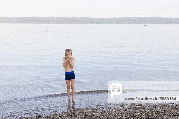Junge bedeckt sein Gesicht am Strand