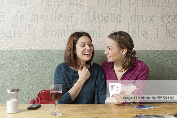Frauen beim Betrachten von Fotos im Cafe