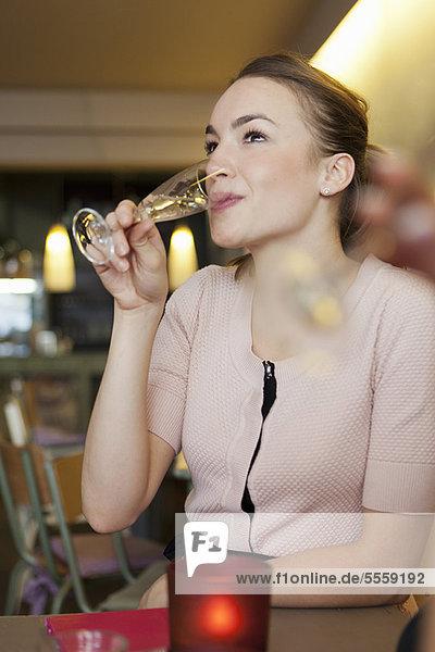 Lächelnde Frau trinkt Champagner im Café