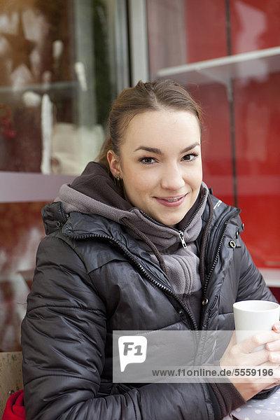 Lächelnde Frau beim Kaffee im Freien