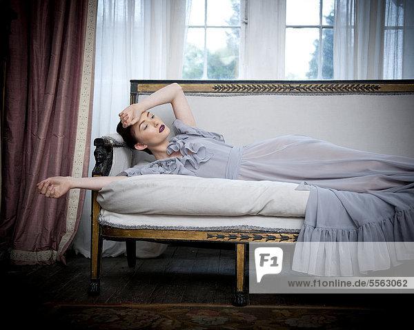 liegend liegen liegt liegendes liegender liegende daliegen Frau Couch lang langes langer lange Kleidung Kleid grau
