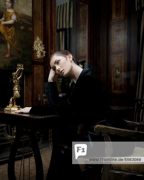 A young woman sitting in a study, looking thoughtful