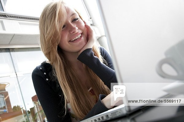 Young female using laptop computer 42-30594587