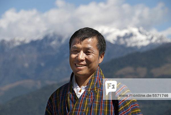 Mann lächelt  Portrait  traditionelle Kleidung Gho  karierter Stoff  Himalaja  Königreich Bhutan  Südasien  Asien