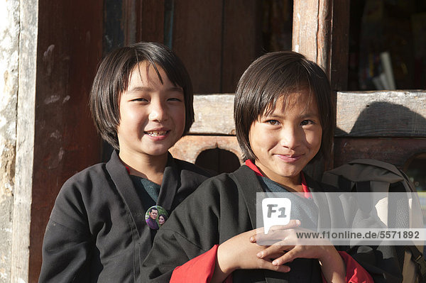 Two smiling girls  portrait  dressed in traditional costume in the village of Thinleygang near Punakha  the Himalayas  Kingdom of Bhutan  South Asia  Asia