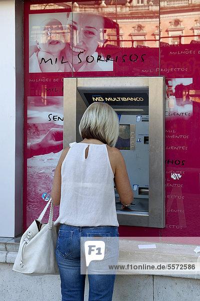 Frau an einem Geldautomat an einer Filiale der portugiesischen Bank Millenium BCP  Banco Comercial Portugues  Portugiesische Handelsbank  in Lissabon  Portugal  Europa