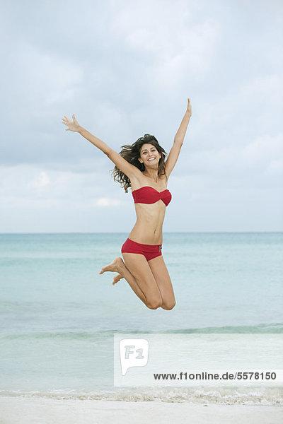 Junge Frau im Bikini beim Springen in der Luft am Strand