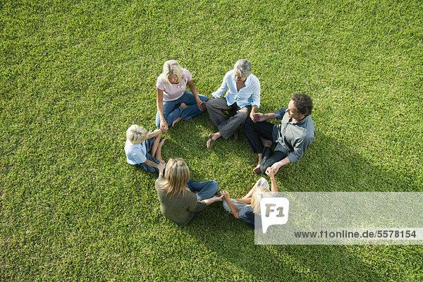 Menschen sitzen im Kreis auf Gras und halten sich an den Händen.