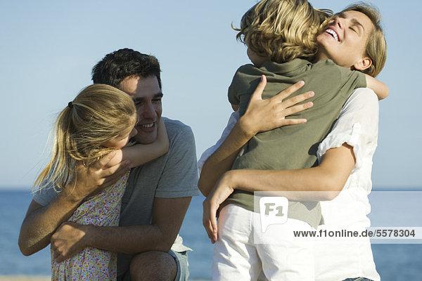 Eltern umarmen Kinder am Strand