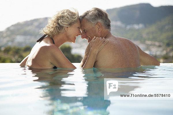 Das reife Paar  das im Pool kuschelt.
