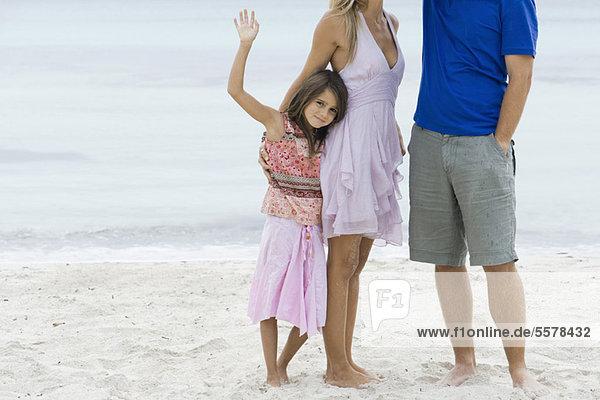 Mädchen und Eltern am Strand stehend  beschnitten