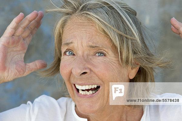 Seniorin mit erhobenen Händen und staunendem Blick
