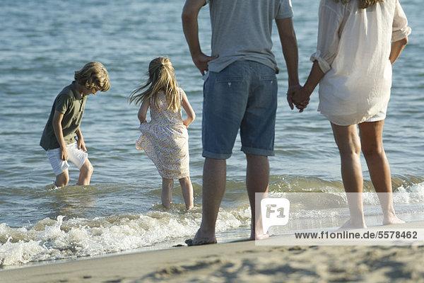 Familie am Strand  Eltern sehen zu  wie Kinder beim Surfen spielen