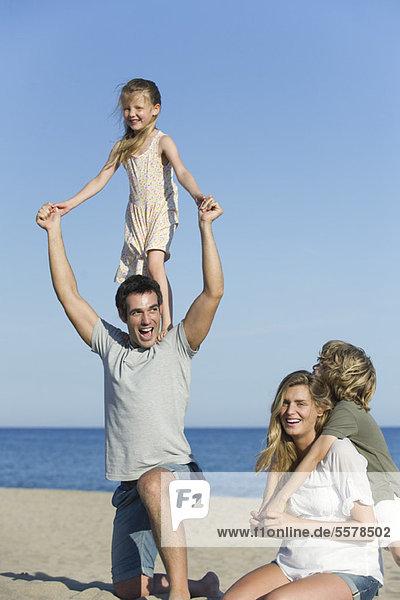 Familie spielt zusammen am Strand  Mädchen steht auf den Schultern ihres Vaters