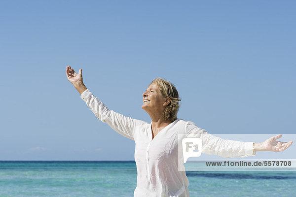 Seniorin auf See mit ausgestreckten Armen  Portrait