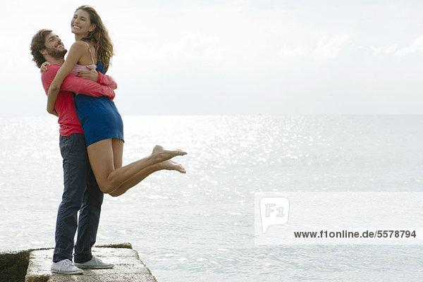 Junger Mann hebt Freundin am Wasser hoch  Porträt