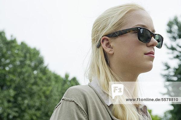 Junge Frau mit Sonnenbrille  die in Gedanken wegschaut