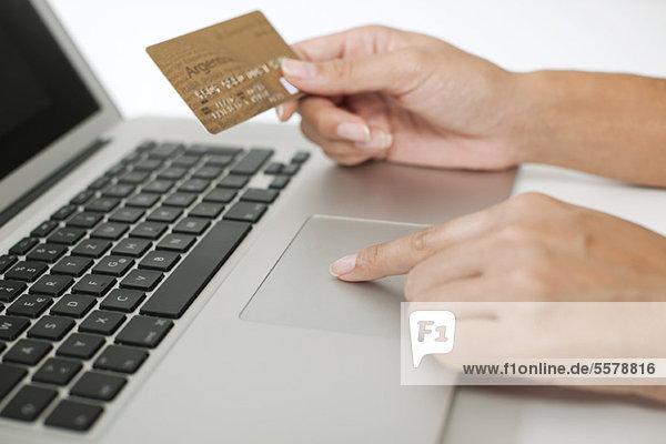 Frau mit Kreditkarte bei der Benutzung des Laptops  beschnitten