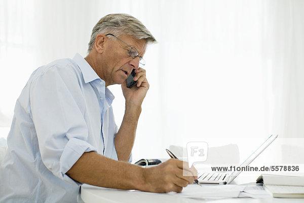 Ein älterer Mann spricht am Handy.