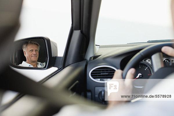 Mann fährt Auto  reflektiert im Seitenspiegel des Fahrers
