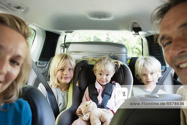 Familie im Auto  lächelnd vor der Kamera