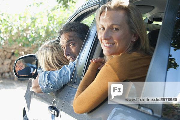 Familie zusammen im Auto  aus den Fenstern lehnend und über die Schultern lächelnd vor der Kamera.
