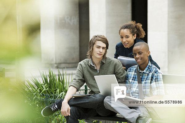 Studenten auf dem Campus mit Laptop