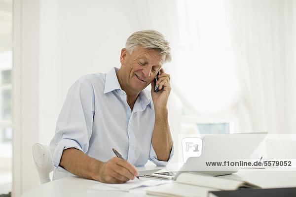 Mann arbeitet zu Hause  telefoniert mit dem Handy
