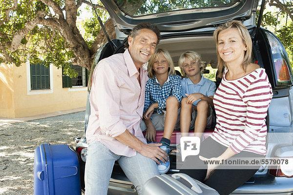 Familie sitzend zusammen im Auto mit offener Heckklappe