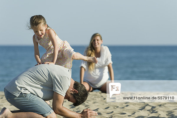 Girl playing with her father at the beach