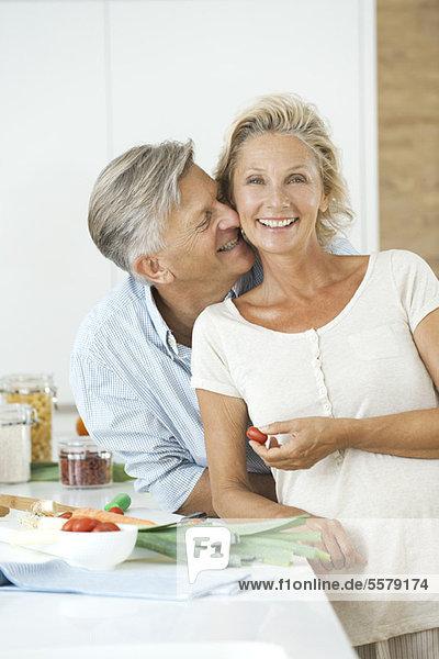 Erwachsenes Paar zusammen in der Küche  Mann kuschelnde Frau  Porträt