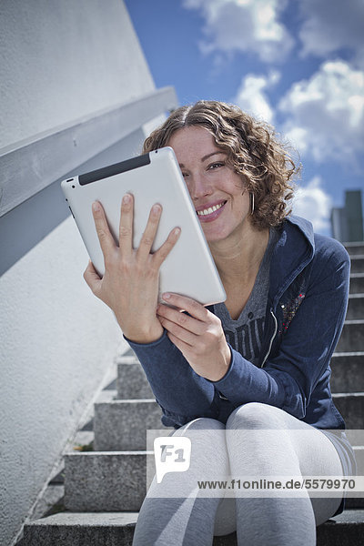 Frau sitzte mit Ipad auf einer Treppe
