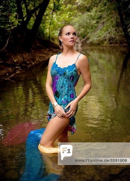 34 year old blond woman in a short flower print dress standing in a small creek looking away from the camera