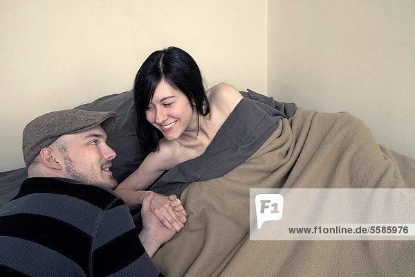 Young woman in bed  holding her boyfriend´s hand
