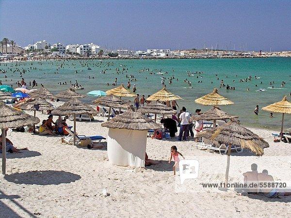 Thatch sunshades line beach holidaymakers cool off Monastir Beach Tunisia