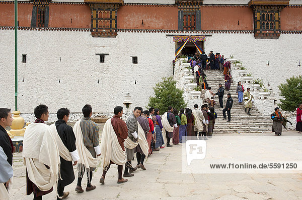 Tibetischer Buddhismus  Festival  Menschen in Gho Tracht stehen in einer Schlange an  Klosterfestung Rinpung Dzong  Paro  Himalaja  Königreich Bhutan  Südasien  Asien
