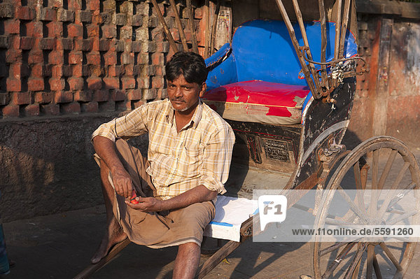 Rickshaw driver sitting and waiting  Chowringhee  Calcutta  Kolkata  West Bengal  India  South Asia  Asia