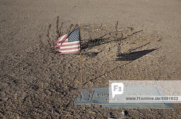 Eine amerikanische Flagge im Memory Gardens Cemetery and Memorial Park  der Friedhof befindet sich in Zwangsvollstreckung und die Bewässerung wurde abgeschnitten  der Sand beginnt bereits  einige der Grabsteine zu bedecken  Brawley  Kalifornien  USA