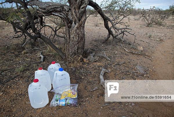 'Wasser und Nahrung für mexikanische Migranten wurde entlang eines Wüstenpfades von Freiwilligen der Gruppe ''No More Deaths'' hinterlegt  Ziel dieser religiösen Gruppierung ist es  die Todeszahlen von Migranten  die die Wüste durchqueren  um in die Vereinigen Staaten zu gelangen zu verringern  seit 1998 sind mehr als 5000 von ihnen gestorben  Arivaca Junction  Arizona  USA'
