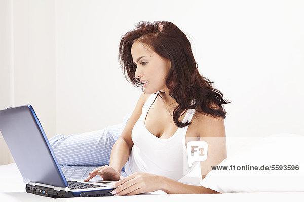 Junge Frau auf dem Bett liegend und mit Laptop
